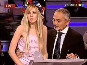 В майке Украина не бордель, в национальном венке, вооруженная плакатом.